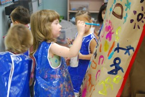 A prekindergartner wearing a blue smock paints at an easel